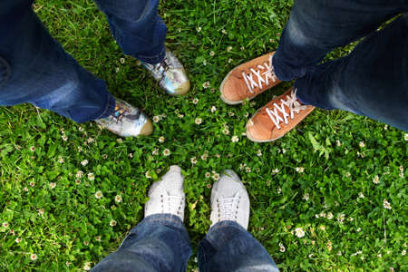 floor standing: Group of friends standing in a circle on a spring meadow but only their feet in sneakers is visible