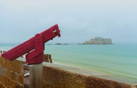 Crimson red coin telescope in foreground and Fort National, ancient fortress on tidal island Petit Be surrounded by turquoise water on misty day in Saint-Malo, Brittany, France