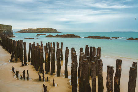Wooden poles along the coastline and tidal island Grand Be with remains of ancient fort and tomb of French writer Chateaubriand in background near Saint-Malo, Brittany, France