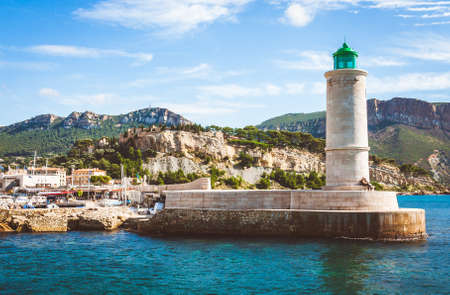 Lighthouse on pier and Chateau de Cassis castle in background on bright sunny day in old port of Cassis, France