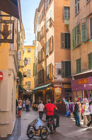 NICE, FRANCE - OCTOBER 13, 2009: Typical narrow street with historic traditional houses, shops and restaurants in old town of Nice 新闻类图片