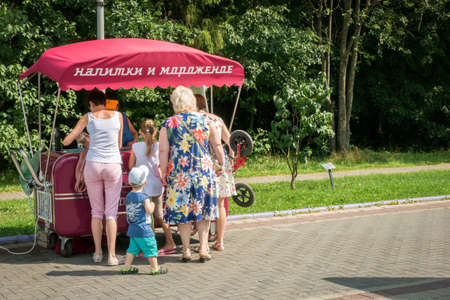 MOSCOW - AUGUST 4, 2018: Women and children buying ice cream in retro van with Drinks and Ice Cream signboard on hot summer day