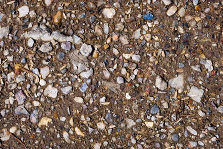 Close up of crushed small stones gravel in brown ground. For texture and background