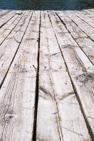 White boardwalk of stripped weathered washed out wooden planks with scratches in perspective near river.
