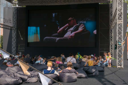 MOSCOW - AUGUST 4, 2018: People relaxing and watching movie on sitting sacks in summer open-air cinema set up in different areas in Moscow as part of Moscow Cinema project