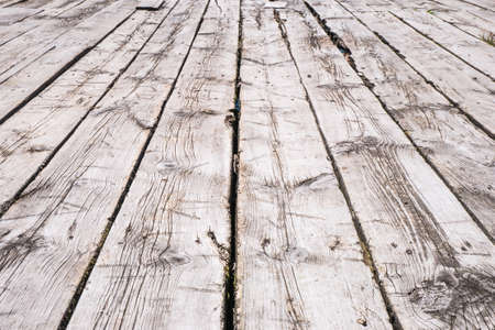 White boardwalk of stripped weathered washed out wooden planks with scratches in perspective. Abstract natural texture background