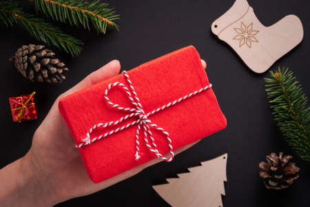 Female hand holding Christmas gift wrapped in bright red paper with striped twine in palm against black background with spruce twigs, pine cone and wooden decorations