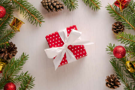 Christmas square present wrapped in red paper with white polka dots and big white bow, surrounded by spruce twigs, pine cones and red and golden decorations. Flat lay style
