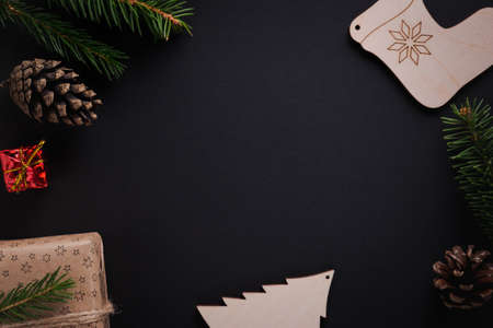 Christmas decorations, pine cones, spruce twigs, gifts on black background with copy space. Flat lay style