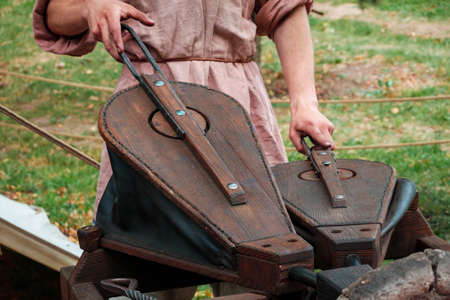 Blacksmith in ancient clothes squeezing bellows to kindle fire in furnace. Reconstruction
