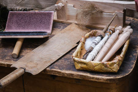 Hand carder, distaff, spindles in bast basket on old wooden table. Traditional fiber preparation tools. Medieval reconstruction Stock Photo