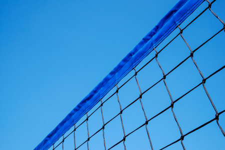 Close up of volleyball net against clear blue sky background. Copy space