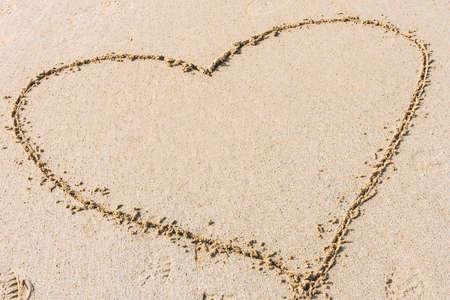 모래 해변에 그려진 하트 모양입니다. 사랑, 낭만적 인 관계의 개념