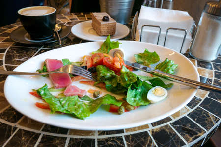 Nicoise salad made of fresh tuna slices, lettuce, hard-boiled eggs and vegetables on white plate, being eaten with fork and knife