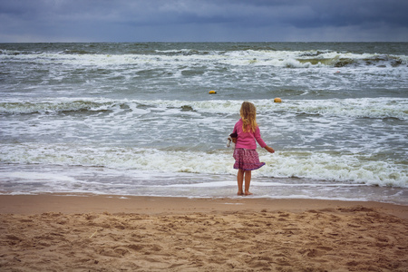 Pretty blond girl on the bank of the rough seas