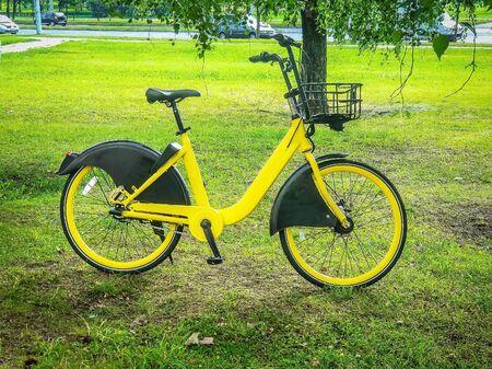 Yellow bike on the lawn, eco-friendly urban transport,