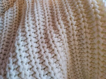 Knitted pattern from white wool. knitted fabric, handmade.