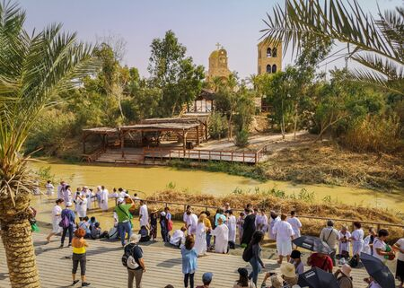 Jordan River, Israel - November, 2019: Pilgrims and tourists on the banks of the Jordan River Редакционное