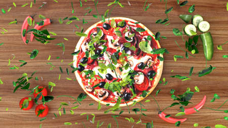 Pizza with salami and olives with ingredient scattered around on wooden table Фото со стока