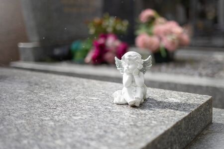 stoned angel at cemetery, graveyard on a bcakground, grave sculpture Stock Photo