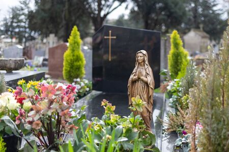 Virgin Mary at cemetery, graveyard background, tombstone
