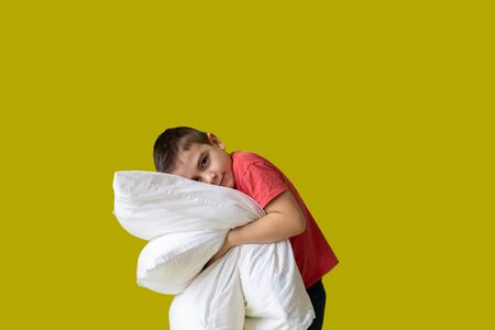 a boy with two pillows, dream, melatonin, insomnia, sleepless yellow background