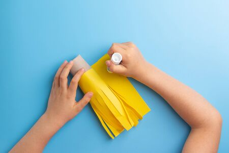 toilet paper roll craft concept for kid and kindergarten, DIY, tutorial, step by step instruction, step2, kids hands hands glue paper Фото со стока