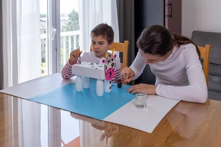 boy makes easy cow paper craft, Mother helping her son to do homework, parents teaching kids at home, boy painting paper cow craft, stay together Фото со стока - 147263213