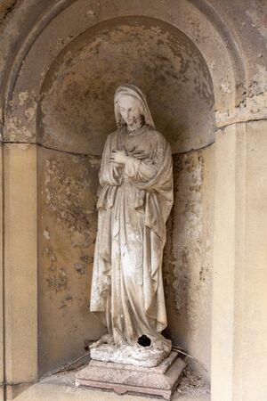 stoned statue of the virgin Mary keeping vigil, grave sculpture