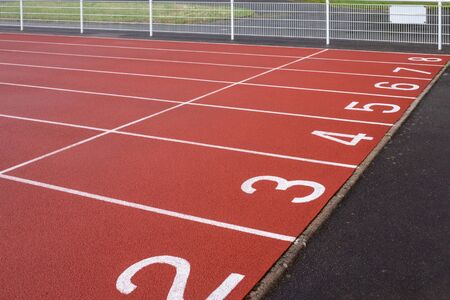 the numbers at start point of running track or athlete track in stadium, running court, red synthetic rubber surface on athletic stadium, sport competition race Фото со стока