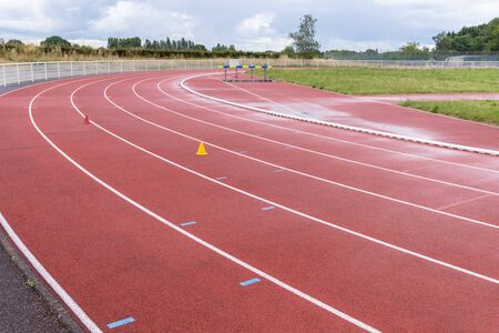 sport stadium for the running practice and the athletic competition, white lines and texture of running racetrack red rubber Фото со стока