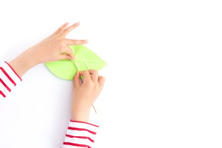 kids hands push strips on a green leaf shape paper detail, simple paper craft for kid and kindergarten, step by step instruction, tutorial, DIY, snail project, step4, Фото со стока
