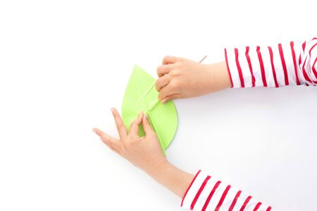 kids hands push strips on a green leaf shape paper detail, simple paper craft for kid and kindergarten, step by step instruction, tutorial, DIY, snail project, step4, stick Фото со стока - 150025181