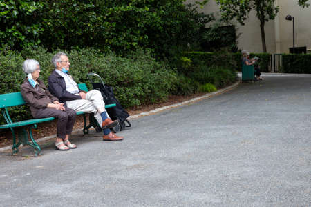 Angers, Maine et Loire/ France - June 20 2020: senior couple wearing protective mask, coronavirus concept, respiratory protection, elderly couple sitting on bench at the park, sensitive age group Éditoriale