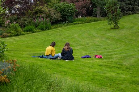 two young women sitting on grass, rear view, girl frends together, students Фото со стока - 149753430