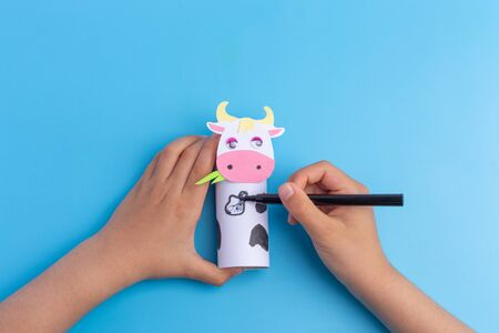 cow craft concept for kid and kindergarten, year of the ox, how to make cow, step by step instruction, tutorial, DIY, toilet paper roll craft, barnyard animal, colorize, kids hands, easy fun project Фото со стока - 150025194