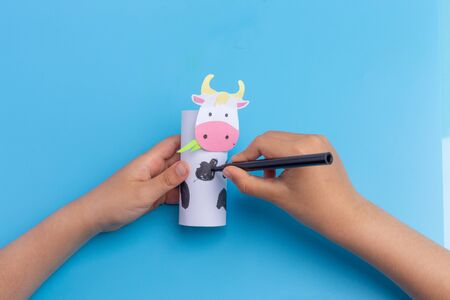 cow craft concept for kid and kindergarten, year of the ox, how to make cow, step by step instruction, tutorial, DIY, toilet paper roll craft, barnyard animal, colorize, kids hands, easy fun project Фото со стока - 150025197
