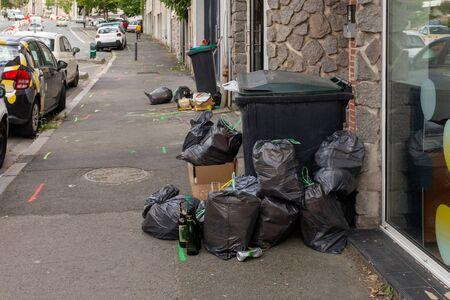 overloaded trash bin on the street, black plastic bag, trash waste