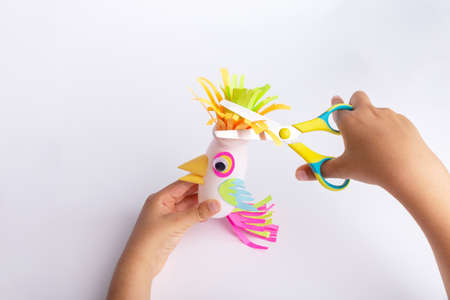 child makes a parrot craft from paper and recycled yogurt bottle, DIY . Kindergarten or school children activity, funny bird craft for kids Фото со стока - 151441591