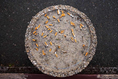 top of a cigarette ashtray outdoor, smoke area, top view, big round ashtray with sand in public place, full of cigarette butts Фото со стока - 151652829