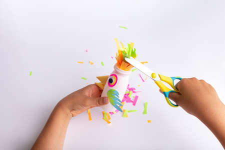 child makes a parrot craft from paper and recycled yogurt bottle, DIY . Kindergarten or school children activity, funny bird craft for kids, kids hands hold scissors Фото со стока - 151689891