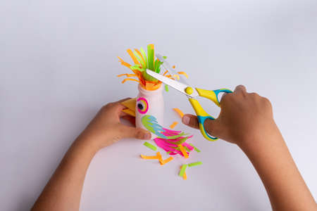 child makes a parrot craft from recycled yogurt bottle, DIY . Kindergarten or school children activity, funny bird craft for kids Фото со стока - 152266473