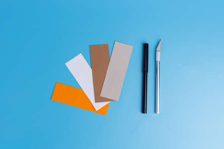 colored paper, cutter and felt-tip pen, blank for childrens creativity, flat lay on blue background, preparation for handmade craft