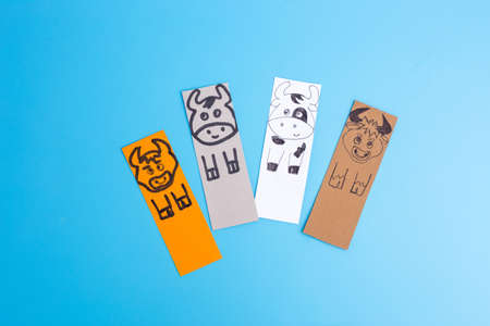 Bookmarks with bull or cow on blue background, handmade paper craft for kids Фото со стока