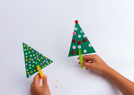 christmas craft for kids. diy, hands making easy paper holiday tree, holiday art activity. Christmas tree concept.