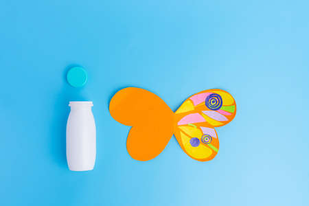 easy butterfly craft from paper and recycled yogurt bottle, DIY . Kindergarten or school, creative craft project ideas, blue background