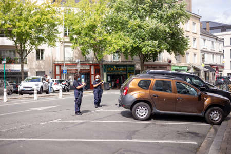 Angers, France - August 22 2020: masked inspectors check parking fees in France, to prevent coronavirus, concept of wearing masks outdoor is mandatory