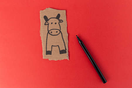 craft cow made of cardboard, How to make bull or ox at home. Children art project. DIY concept. making toy on red. Step by step photo instruction. Step 1 Stock Photo