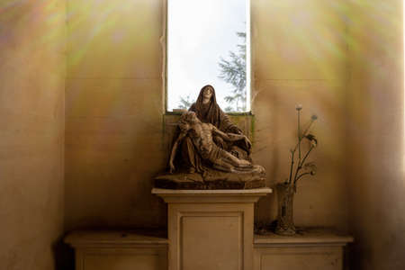 cemetery vintage sculpture of madonna, tombstone, sadness concept, catholic community, holy light ray effect