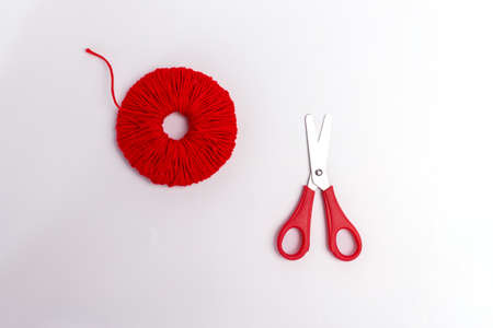 making red pompons from thread, top view, white background, handmade craft